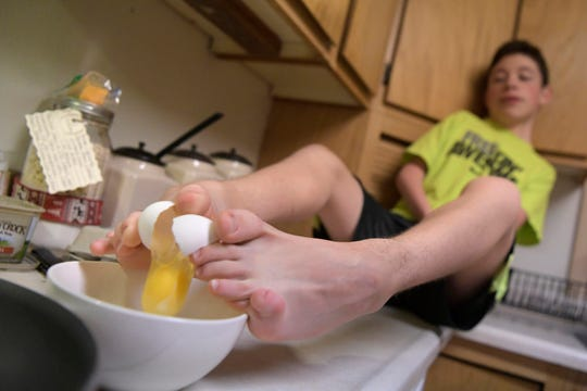 """In this Friday, Dec. 14, 2018, photo, Devin McLane prepares breakfast in Corvallis, Mont. What most would use their hands for, Devin uses his feet. """"...If you can do it with your hands, I can do it with my feet,"""" he said. """"I use mine to eat, to write, to draw, to cook."""" he said as he prepared breakfast for dinner the night before his first high school meet."""