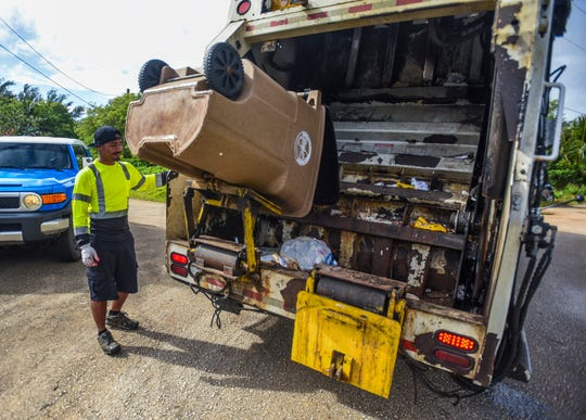 A Guam Solid Waste Authority employee empties a cart of household waste into the back of a compactor truck in Malojloj in this Dec. 13, 2018, file photo.