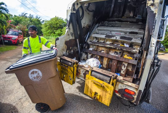 A Guam Solid Waste Authority employee returns a trash cart back to the curbside after emptying its contents of household waste into the back of a compactor truck in Malojloj in this Dec. 13, 2018, file photo.