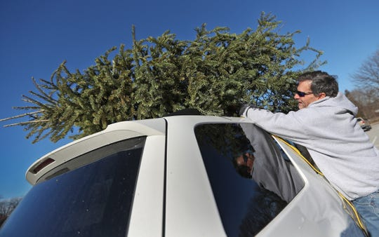 Jim Marten grabs his Christmas tree to drop off at Broad Ripple Park, Wednesday, Dec. 26, 2018.  The Indianapolis Department of Public Works (DPW) and Indy Parks are accepting live Christmas trees, from Marion County residents, at multiple drop-off points, like this one, through Thursday, Jan. 31, 2019.  The trees must be free of decorations and stands.  The trees are recycled for sustainable landscaping resources, such as mulch and soil blends.