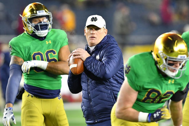Fighting Irish offensive coordinator Chip Long works with players during warmups before the game against the Florida State Seminoles at Notre Dame Stadium.