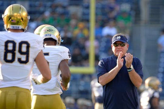 Irish coach Brian Kelly (right) watches the Irish warm up before the game against the Navy Midshipmen at SDCCU Stadium.