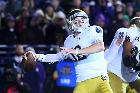 Fighting Irish quarterback Ian Book (12) drops back to pass against the Northwestern Wildcats during the second half at Ryan Field.
