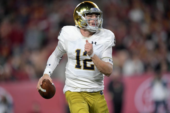 Notre Dame Fighting Irish quarterback Ian Book (12) throws a pass against the Southern California Trojans in the second quarter at Los Angeles Memorial Coliseum.