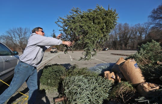 Jim Marten tosses his Christmas tree into a pile of other trees at Broad Ripple Park, Wednesday, Dec. 26, 2018.  The Indianapolis Department of Public Works (DPW) and Indy Parks are accepting live Christmas trees, from Marion County residents, at multiple drop-off points, like this one, through Thursday, Jan. 31, 2019.  The trees must be free of decorations and stands.  The trees are recycled for sustainable landscaping resources, such as mulch and soil blends.  Broad Ripple, Ellenberger, Garfield, Gustafson, Krannert, Northwestway, Perry, Riverside, and Sahm Parks are drop-off locations.
