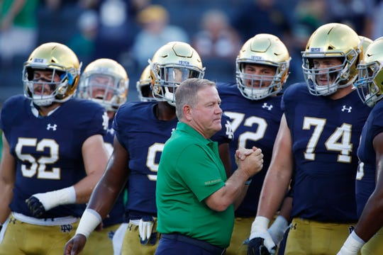 Fighting Irish coach Brian Kelly talks to his team before the game against the Michigan Wolverines at Notre Dame Stadium.