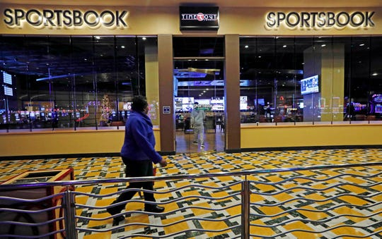 In this Dec. 18, 2018 photo, a woman walks by the Time Out Lounge at the Pearl River Resort, in Philadelphia, Miss. The sports book owned by the Mississippi Band of Choctaw Indians is the first to open on tribal lands outside of Nevada following a U.S. Supreme Court ruling earlier this year, a no-brainer business decision given the sports fans among its gambling clientele.