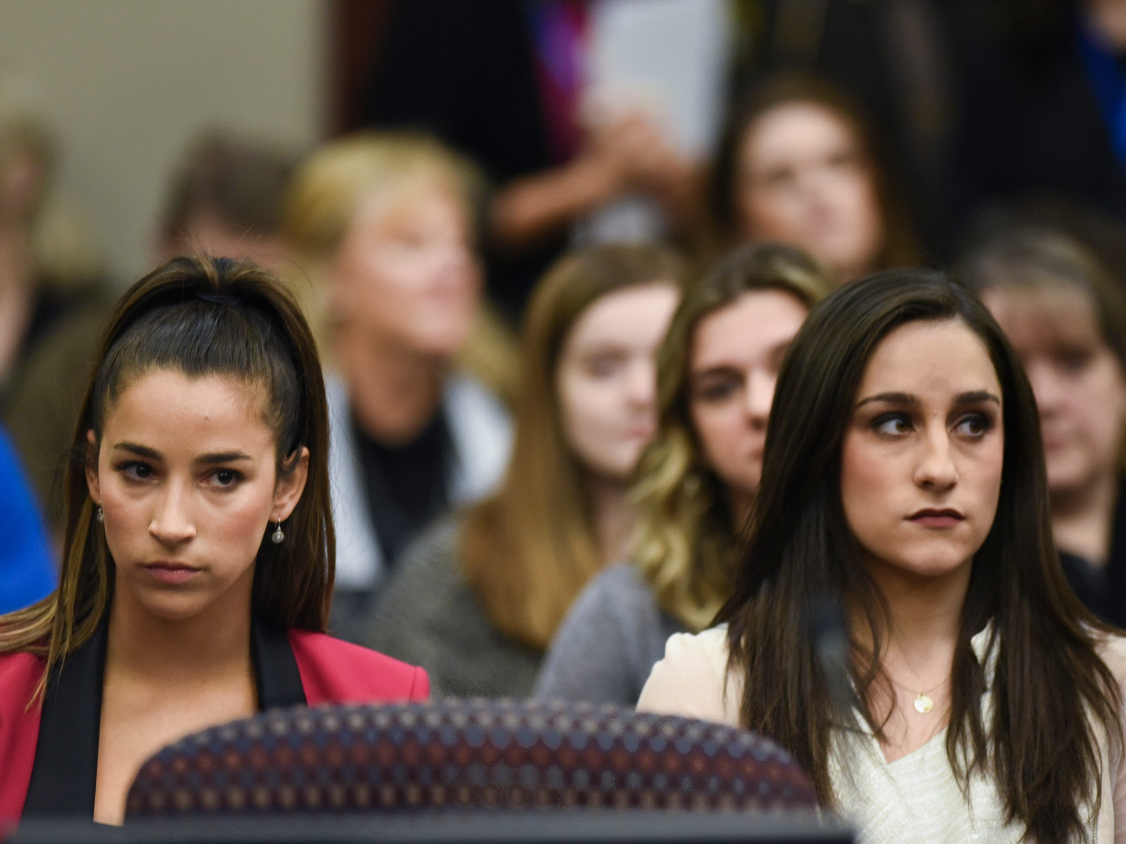 Former Olympians Aly Raisman, left, and Jordyn Wieber sit in Circuit Judge Rosemarie Aquilina's courtroom Friday, Jan. 19, 2018, during the fourth day of victim impact statements regarding former sports medicine doctor Larry Nassar, who pled guilty to seven counts of sexual assault in Ingham County, and three in Eaton County.