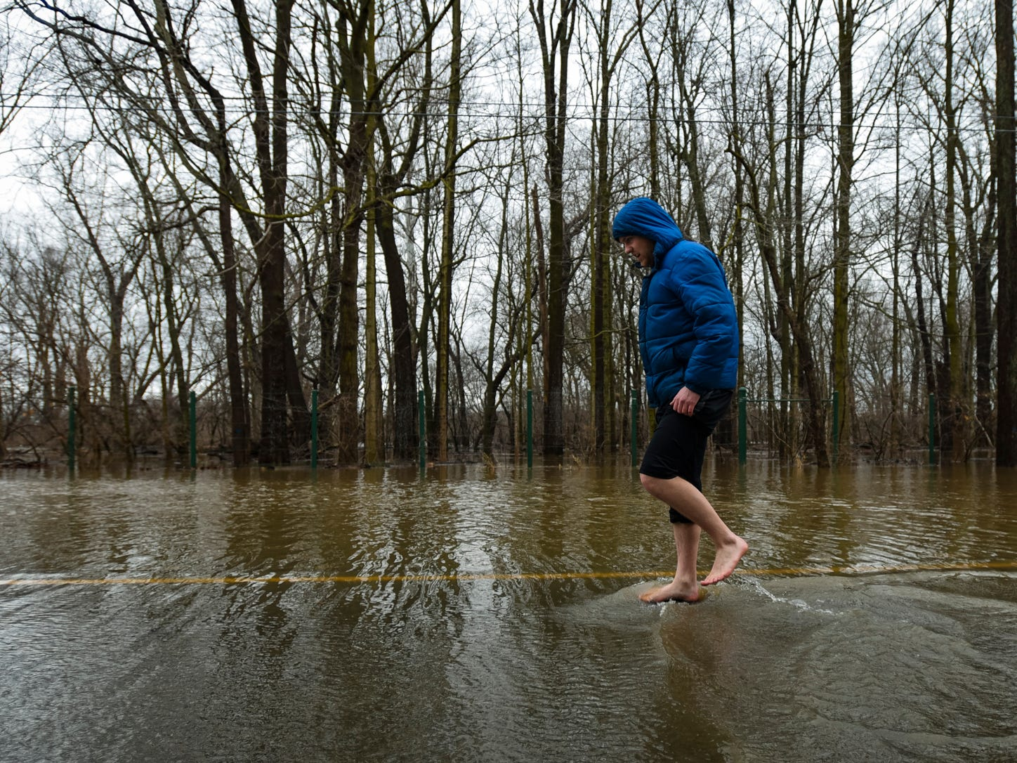 """The water is so cold, it hurts - it really, really hurts,"" LCC student Matt Lorenz said after taking off his shoes and socks to walk through water that covered the road on Kalamazoo St. between Marigold and Clippert Wednesday, Feb. 21, 2018, closed to traffic after the Red Cedar River crested and flooded low-lying areas."