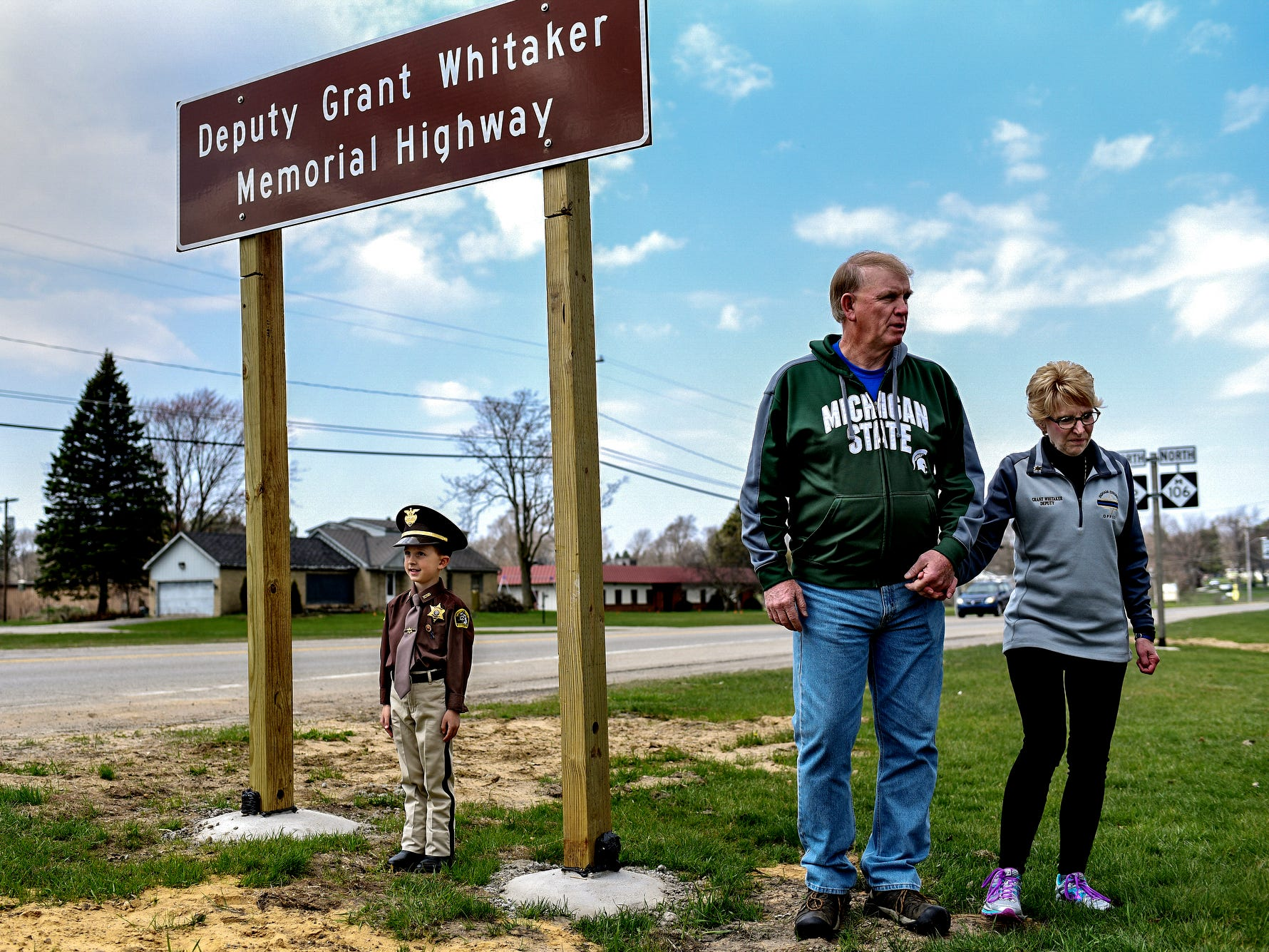 "Ingham County Sheriff's Deputy Grant Whitaker's nephew Henry Whitaker, 5, poses under a traffic sign honoring his late uncle while dressed as an Ingham County Sheriff's Department deputy as Deputy Grant Whitaker's parents Clyde, center, and Mary stand by after a ceremony unveiling the sigh that renames a portion of Highway M-52 in Stockbridge Township as ""Deputy Grant Whitaker Memorial Highway"" on Friday, April 27, 2018. Deputy Whitaker was killed in the line of duty after crashing during a high speed chase in December of 2014. Ingham County Sheriff Scott Wriggelsworth also commemorated the event by renaming April 27th as ""Deputy Whitaker Day"" in his honor."