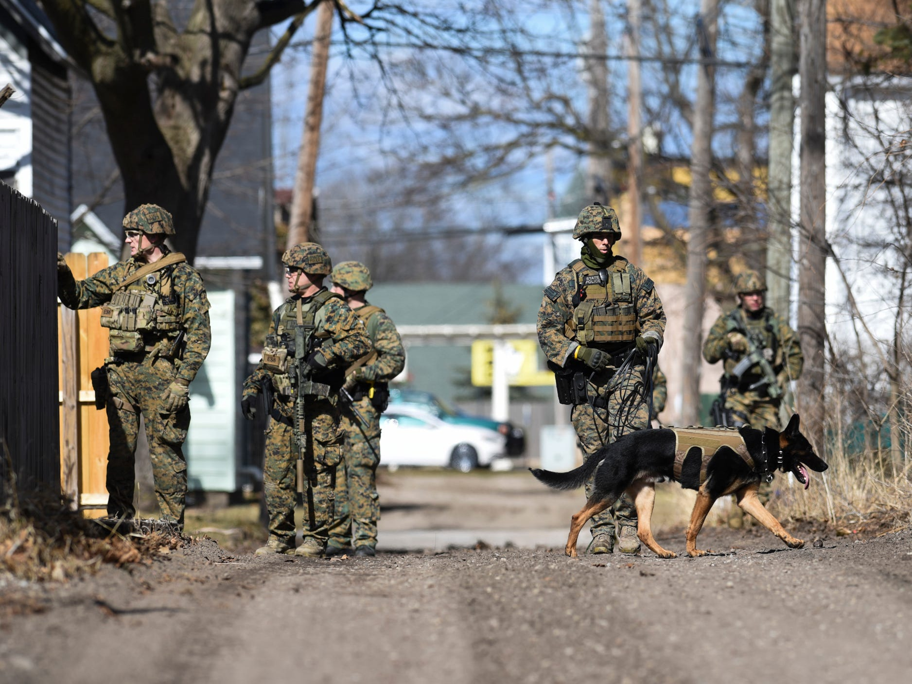 Members of the Michigan State Police ES (Emergency Support) team search neighborhoods adjacent to the Central Michigan University campus Friday, March 2, 2018, for James Davis Jr., 19, who reportedly shot and killed his parents in a dorm on campus earlier in the morning.  After a nearly daylong manhunt, the man was taken into custody early Saturday morning.