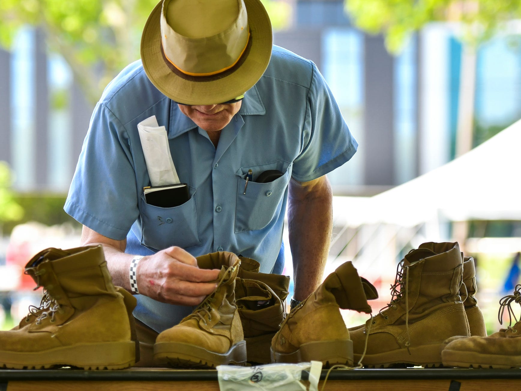 Ed Eitelbuss of Lansing searches for a pair of boots in his size, Wednesday, May 23, 2018, at Adado Riverfront Park in downtown Lansing during the 15th Annual Capital Area Stand Down for Homeless Veterans.  The event brings together services at a single location to provide resources for homeless veterans, and those at risk of becoming homeless.  Just over 50 area agencies were in attendance to provide health screenings,  shots, benefits enrollment, employment help, housing help, and clothing.  The event is put on by Volunteers of America Michigan in partnership with the US Department of Veteran Affairs.
