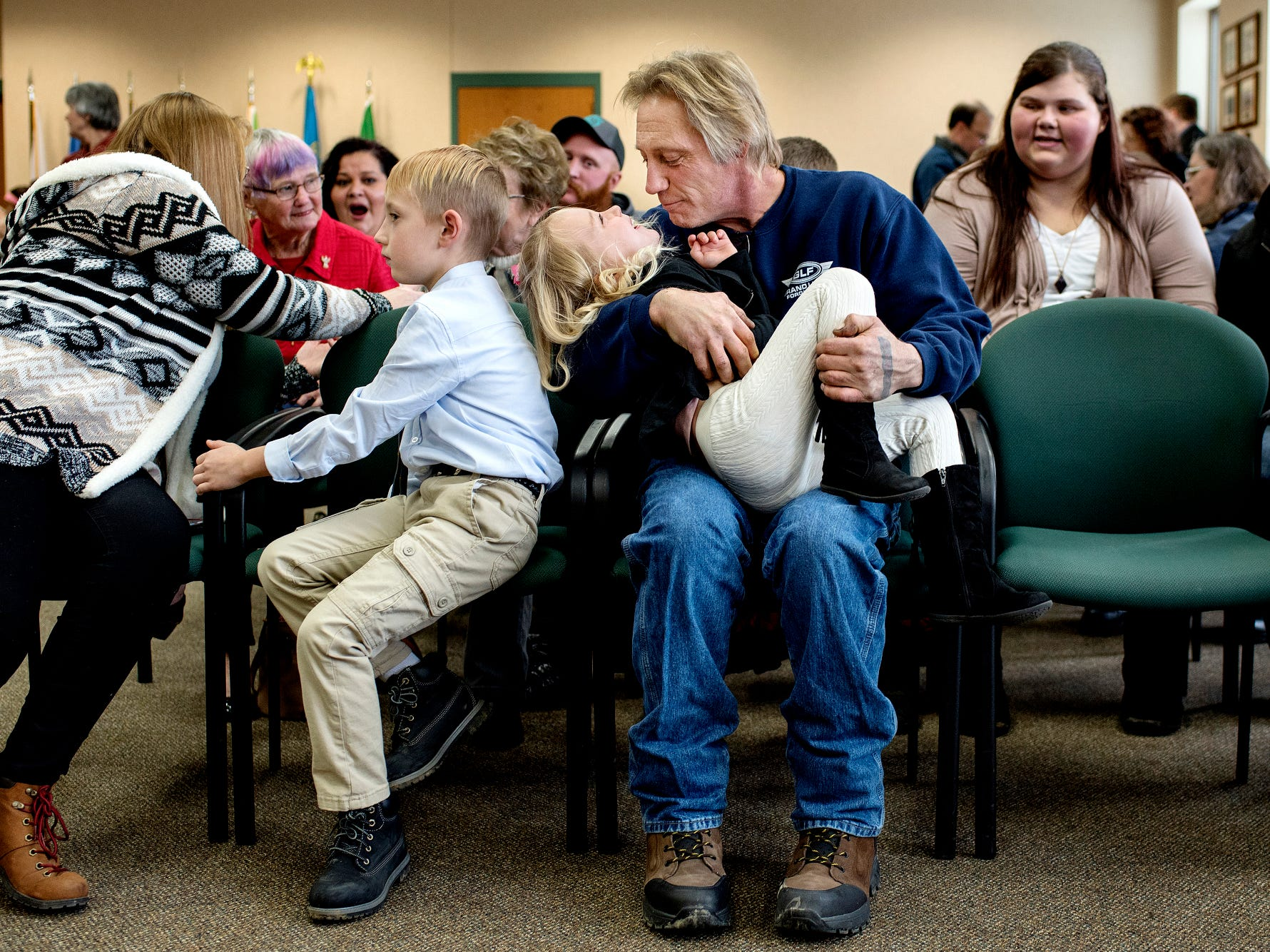 Durwood Fletcher, right, cradles Alayna, 4, as he and his wife Lisa, left, prepare to finalize the adoption of Alayna and her 7-year-old brother Austin, second from left, during a Michigan Adoption Day ceremony at the Clinton County Courthouse in St. Johns. Four families finalized the adoptions of six children.