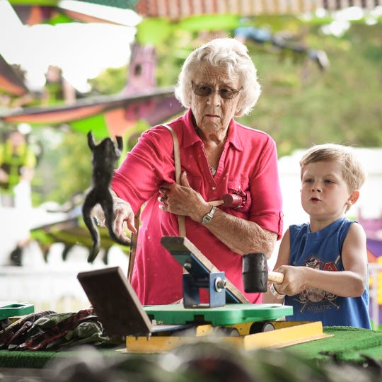 "Seven-year-old Wyatt Brown of Dansville gets some pointers from great-grandmother Eva Brown, Wednesday, Aug. 1, 2018, while playing ""Frog Bog"" on the runway at the 164th Ingham County Fair in Mason.  Ingham, Eaton and Clinton county fair boards are wrestling with how they will ensure safety at their fairs this summer during the COVID-19 pandemic."
