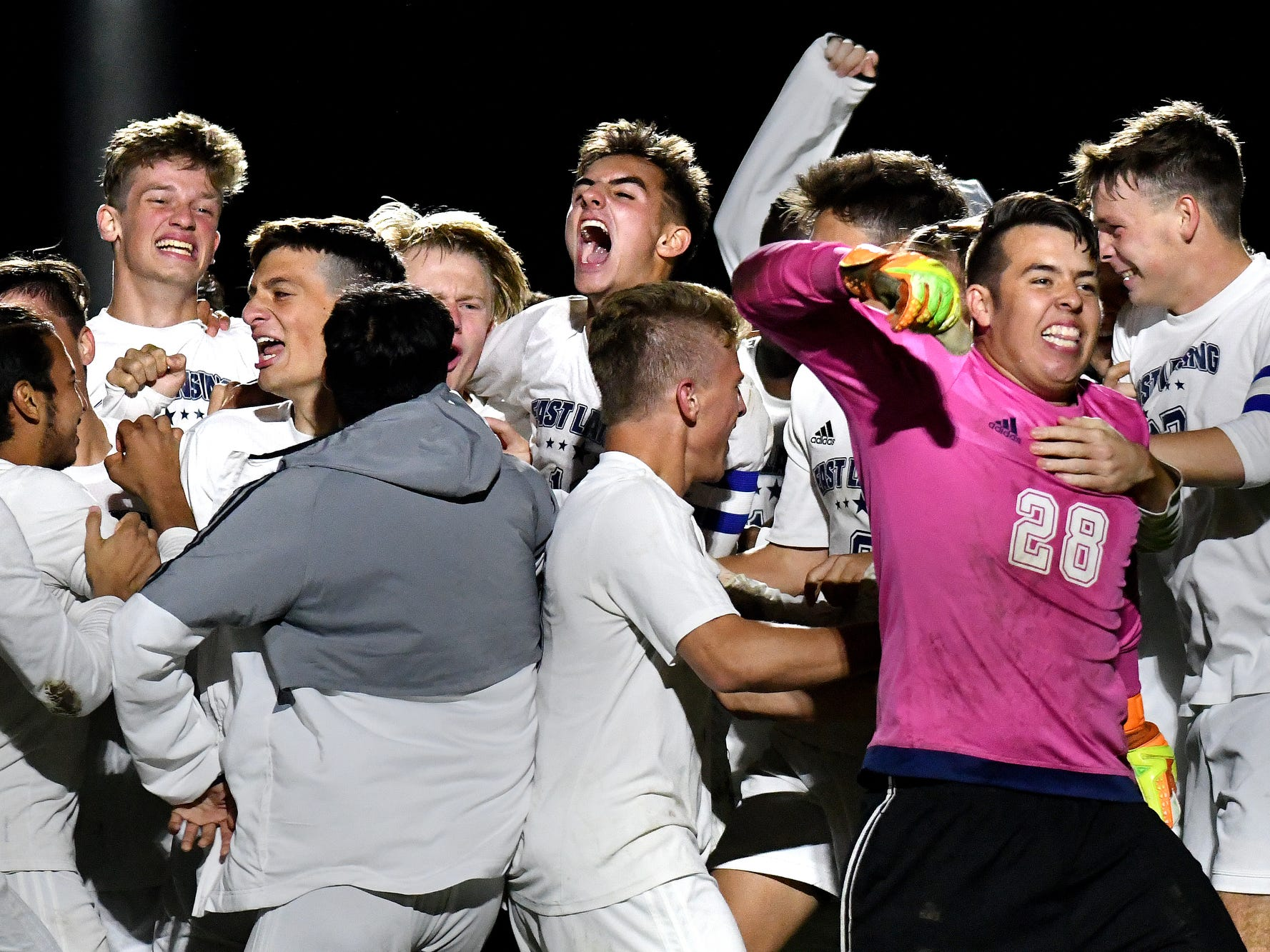 East Lansing's soccer team celebrates after beating Okemos after a shootout on Thursday, Oct. 4, 2018, in the Gold Cup semifinal match at Okemos High School.