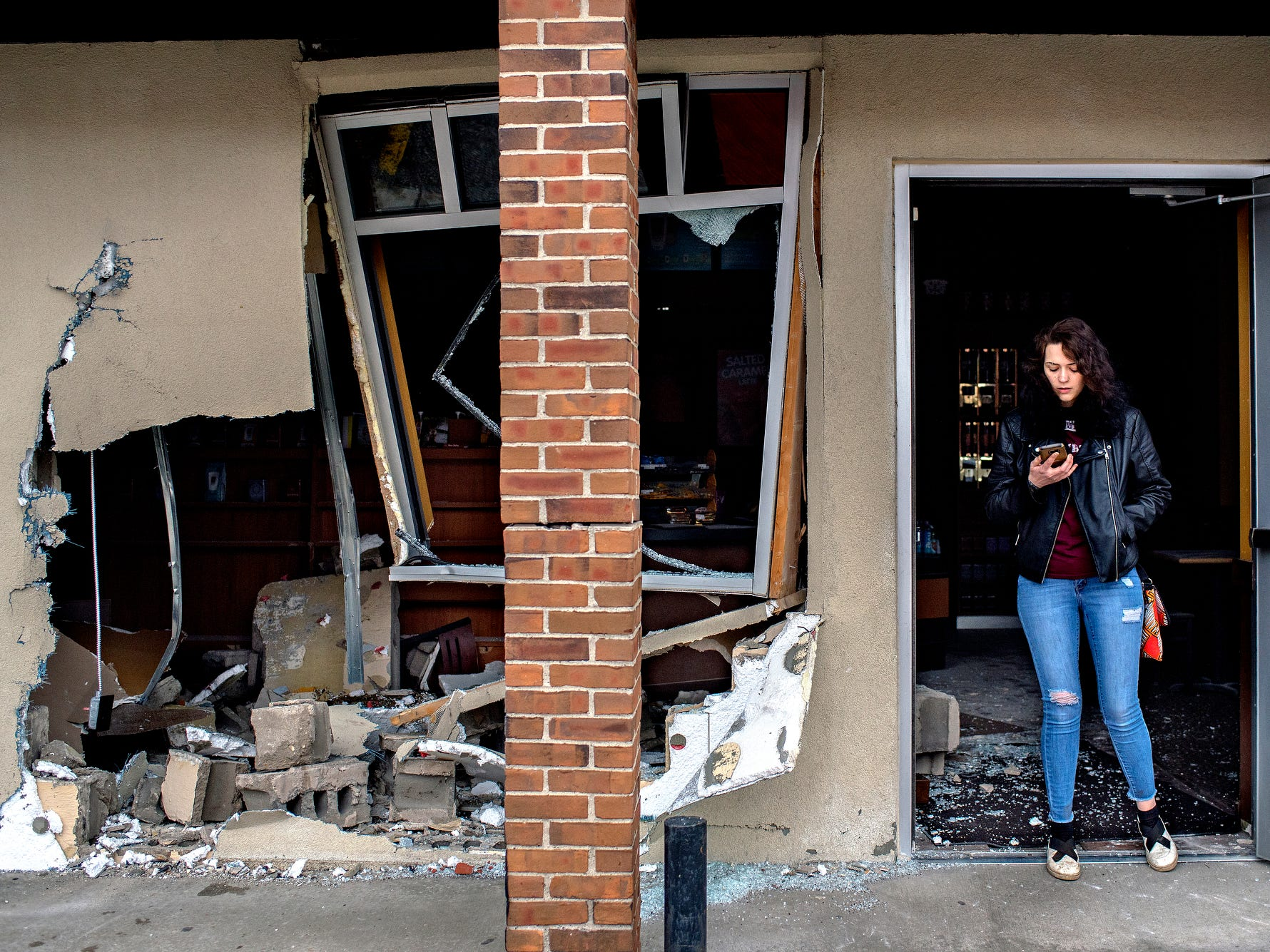 Employee Stacie Tomkins stands in the doorway next to the site where a car crashed into the Biggby on South Cedar Street at the Holt Road intersection on Friday, April 13, 2018, in Holt. An elderly woman trying to leave a parking space had her car in drive instead of reverse causing her to drive through the building near the entrance. No one was hurt in the crash.