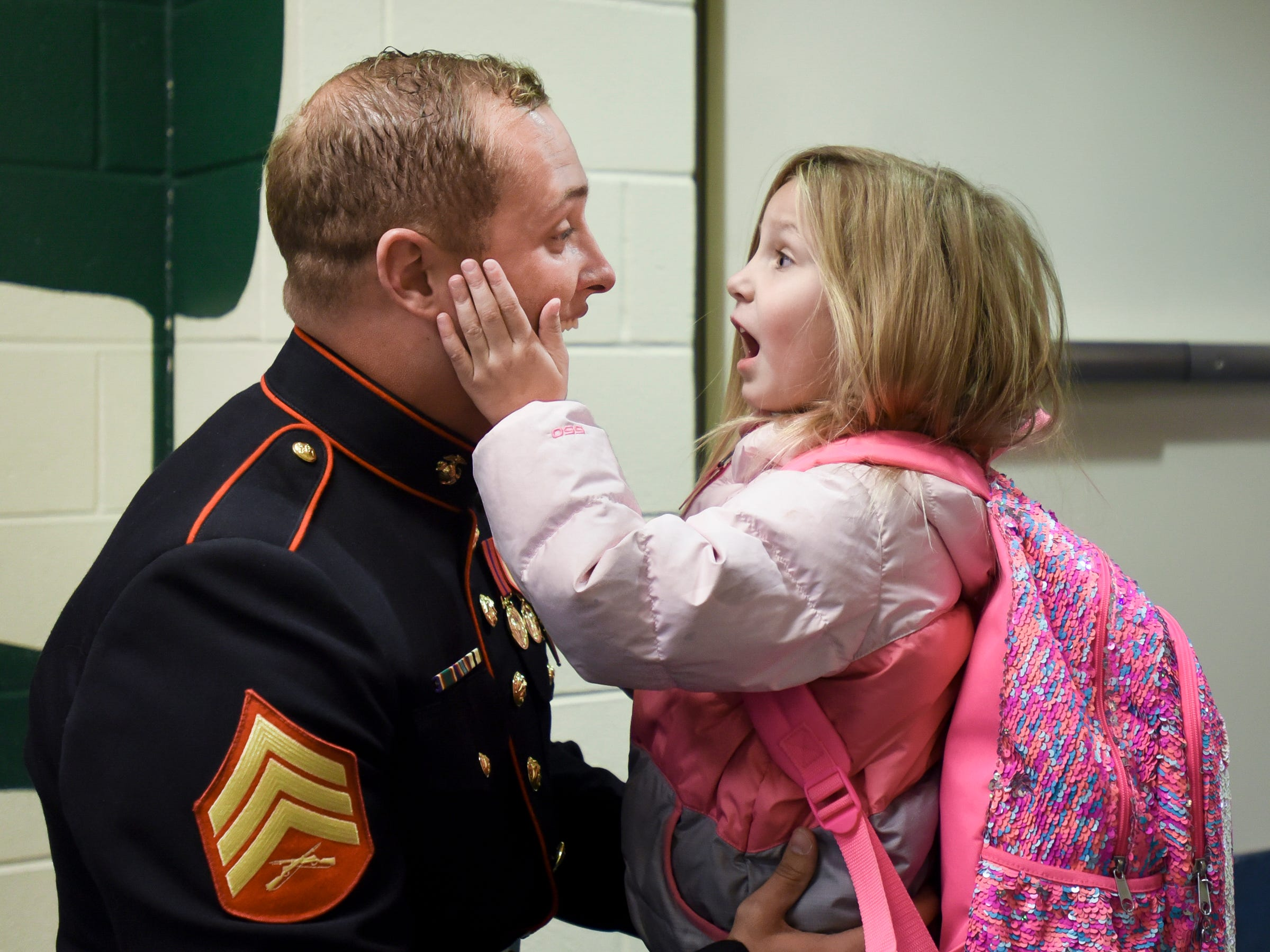 Tears fall from Marine Sgt. Cameron Spiece's eyes, as four-year-old daughter Graycen cups his face, Thursday afternoon, Oct. 25, 2018, at Oakview South Elementary School in St. Johns.  Sgt. Spiece was discharged Wednesday, after spending about a year recovering from a traumatic brain injury caused when a rocket blew up in his face during combat training in North Carolina.  Sgt. Spiece also suffered hand and nerve damage due to the accident.  He has been in the Marine Corps for the past six years.
