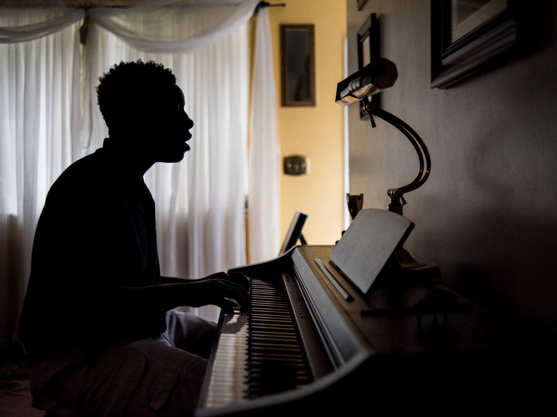 Kemar Williams, 15, a sophomore at Everett High School plays piano Monday evening, Aug. 20, 2018, where he and his two brothers live with their grandmother.