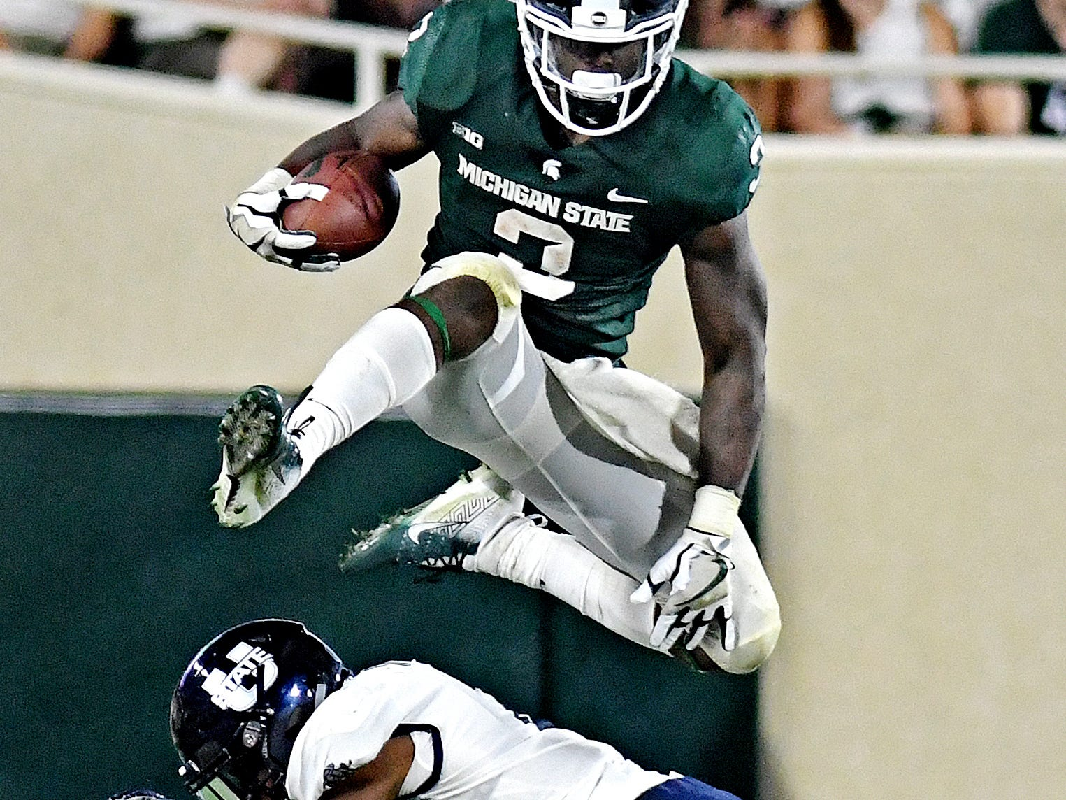 Michigan State's LJ Scott leaps over Utah State's Ja'Marcus Ingram on a run during the fourth quarter on Friday, Aug. 31, 2018, at Spartan Stadium in East Lansing.