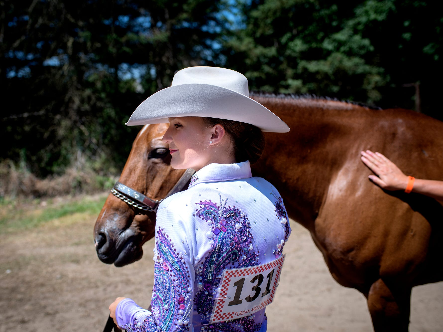 Eaton Rapids Middle School 8th-grader Lauren Malone stands with her 20-year-old quarter horse, Rudy, before competing in the 12 and under 4-H Horse Showmanship event at the Eaton County Fair on Monday, July 9, 2018, in Charlotte. Malone belongs to the Eaton Equestrians 4-H Club. The Eaton County Fair, which  runs July 9-14, features carnival rides, live entertainment, demolition derby, horse races, tractor pulls, area Future Farmers of America competitions and agricultural events.