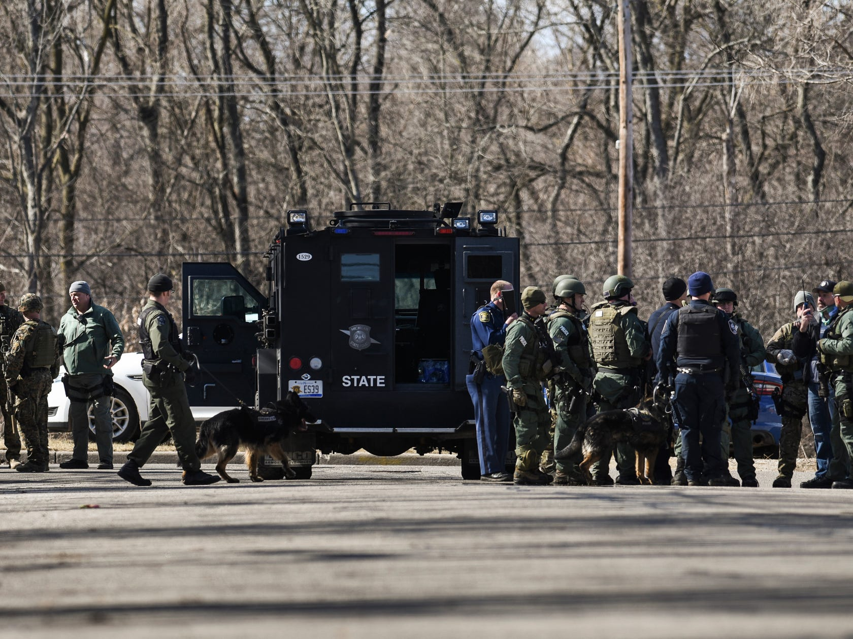 Law enforcement, including the Michigan State Police ES (Emergency Support) team prepare to search neighborhoods adjacent to the campus of Central Michigan University for James Davis Jr., on Friday, March 2, 2018, after he reportedly shot and killed his parents in a dorm on campus earlier in the morning.