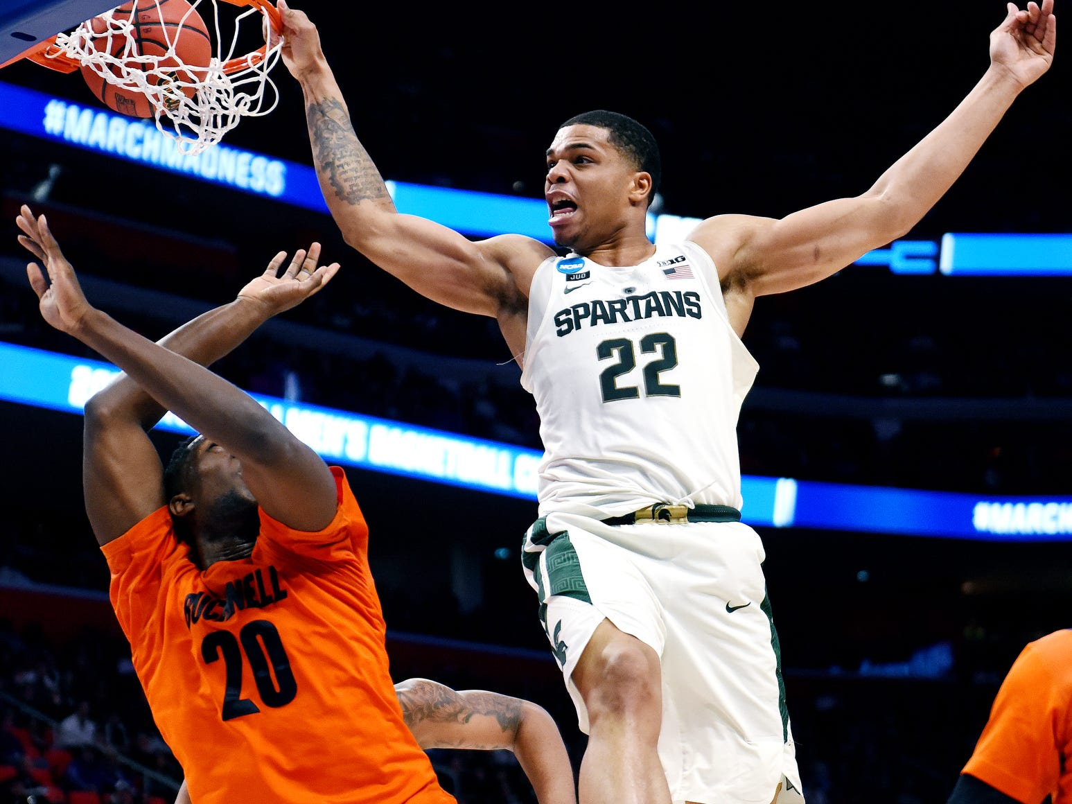 Michigan State's Miles Bridges, right, dunks over Bucknell's Nana Foulland during the second half on Friday, March 16, 2018, at the Little Caesars Arena in Detroit. The Spartans beat Bucknell 82-78 to advance to the second round in the NCAA tournament.