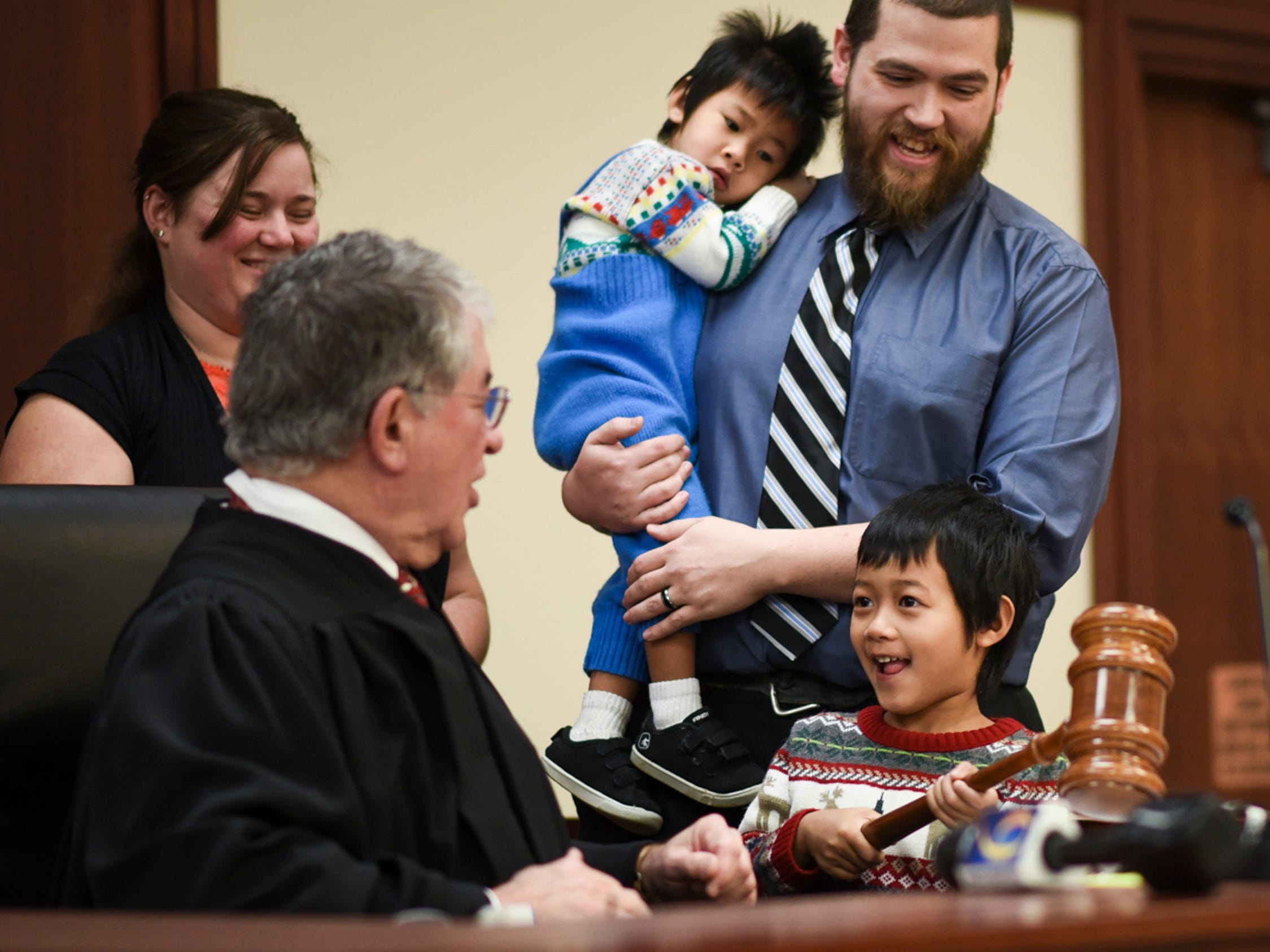 Five-year-old Nathanael Blakely of Mason, gets a chance to use Ingham County Probate Judge George Economy's special Christmas gavel during a hearing that made adoptions of himself and his 2-year-old brother Owen official, Tuesday, Dec. 18, 2018, at Veterans Memorial Courthouse in Lansing.  Economy has held adoption week 32 of his 33 years on the bench.  This is his final week before retiring.  Also pictured are Mark and Emily, the boys' parents.