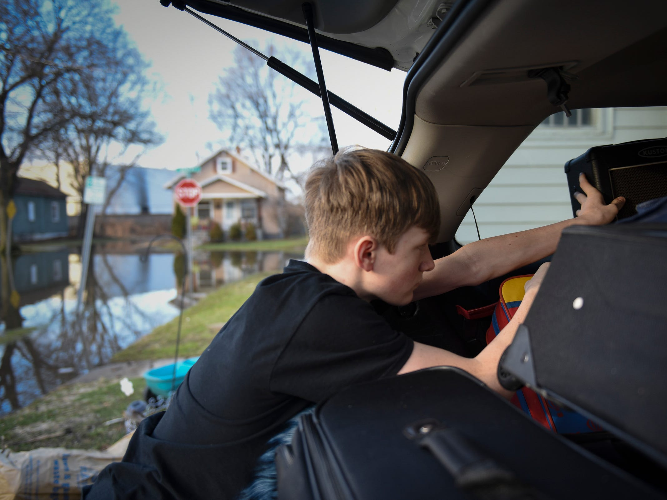"Chance Mauldin, 14, of Lansing, loads up his bass guitar and amplifier as he and the rest of his family prepare to evacuate their home in the 800 block of Beulah in the Baker-Donora neighborhood., Thursday afternoon, Feb. 22, 2018.  His mom Crystal will be taking him, three sisters, and their dog to a local hotel.  She is trying to turn the flooding tragedy into a ""mini-vacation.""  The kids are excited about swimming, despite the swimmable waters due to flooding within her neighborhood.  Crystal said she's excited about the hot tub."