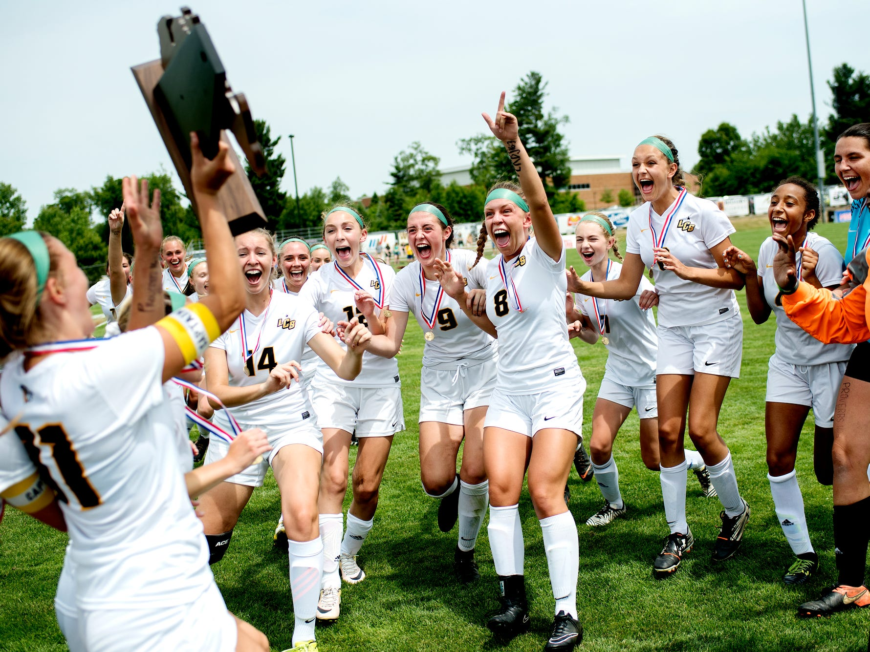 Lansing Christian's Kasey Jamieson, left, presents the Division 4 championship trophy to the team as they celebrate their win on Friday, June 15, 2018, at Williamston High School. Lansing Christian won the Division 4 girls soccer championship by defeating Kalamazoo Christian 1-0.