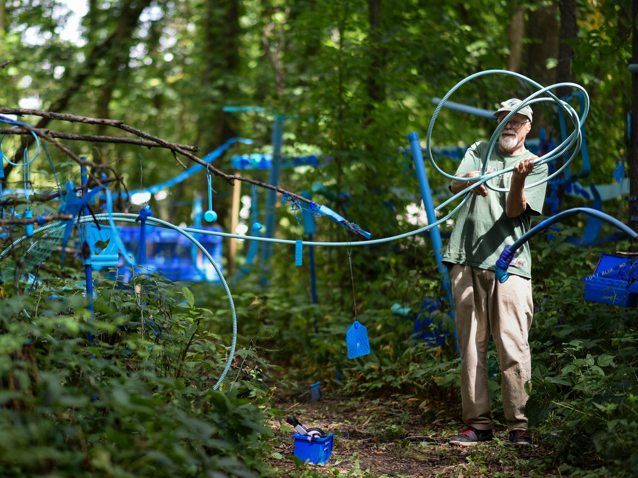 "Artist Robert Park of Bath works on ""The Blue Loop,"" a 1,000-foot art installation on his property in the woods behind his home, Thursday, Aug. 30, 2018.   In May, the township ordered him to clean up the installation he's worked on for over two years.  Officials say it's ""junk.""  Parks meekly responds saying it is art.  A hearing is set for Oct. 31 in Clinton County District Court where a judge will determine if his installation violates the township's anti-junk ordinance."