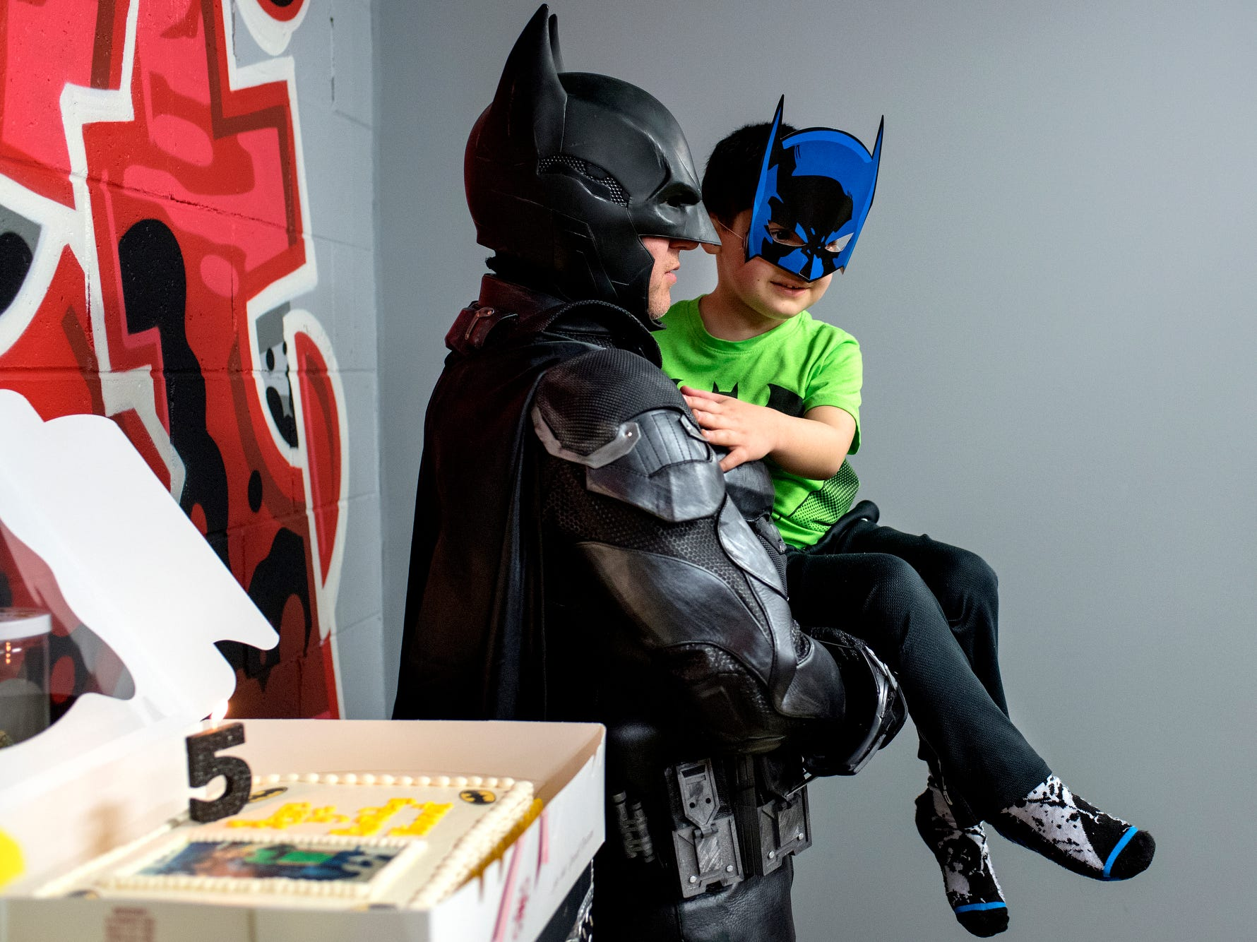Shamus Smith, dressed as Lansing Batman, left, holds 5-year-old Vincent Gentile while guests sing him happy birthday during his birthday party on Saturday, March 24, 2018, at the District5 Extreme Air Sports trampoline park in Lansing. Members of the League of Enchantment dressed as superheroes and attended Gentile's birthday. Gentile is recovering from retinoblastoma, a rare eye cancer.