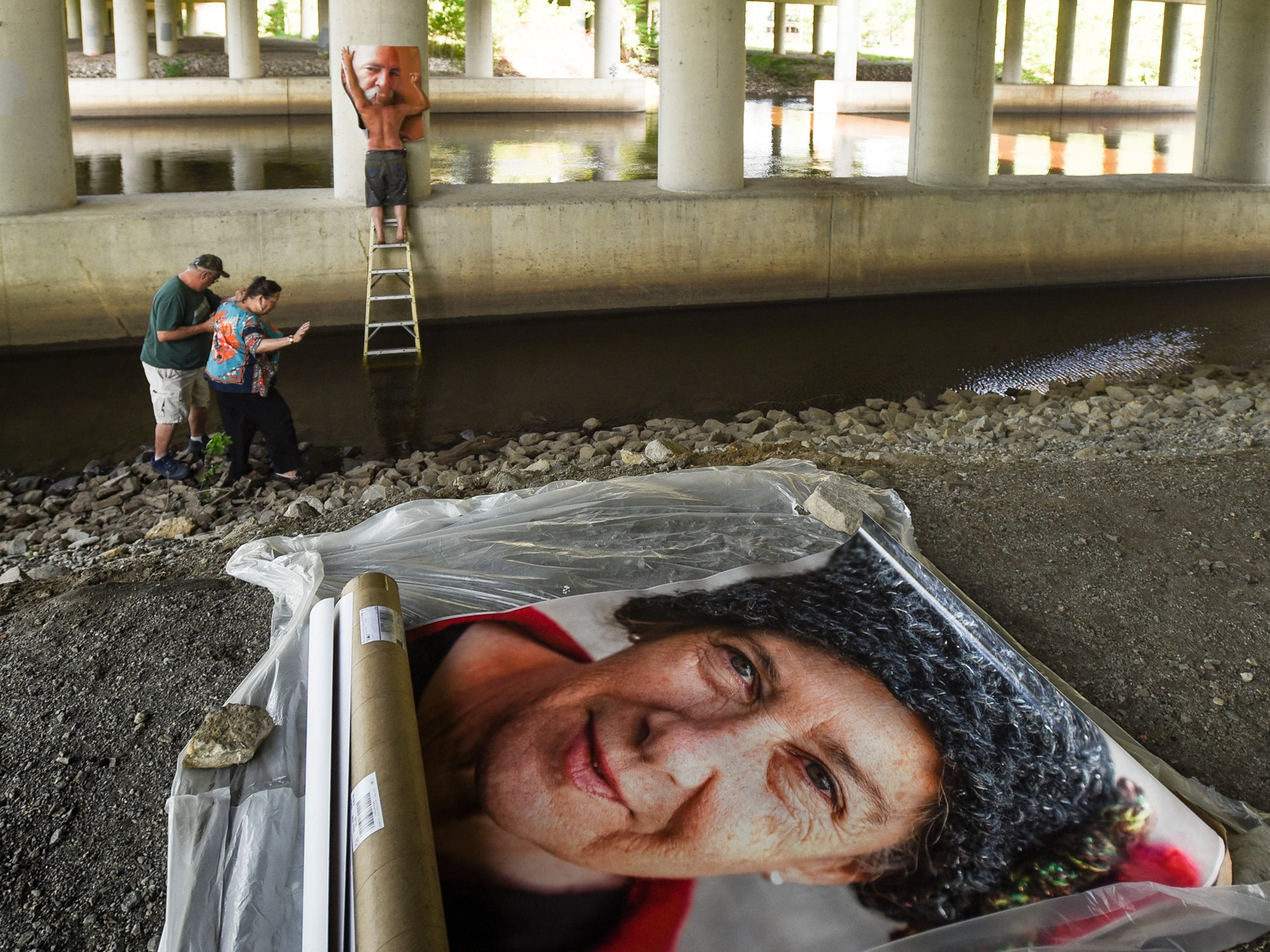 "Jim Mathews, left, helps Lansing artist Gigi Morton down an embankment on the Grand River beneath the 496 overpass, Thursday, May 31, 2018, to help her son Caleb Kisor, right, affix one of 10 4-foot by 5-foot photographs of veterans she met in San Franscisco at the American Legion War Memorial  Commission last year.  Her project is called ""The Forgotten Ones ... The Vets of ..."" She is one of ten ARTpath artists showing work along a 3.5 mile stretch of the Grand River."