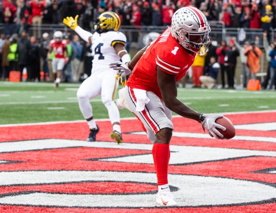 Johnnie Dixon caught this 31-yard touchdown pass in the 62-39 rout of Michigan.