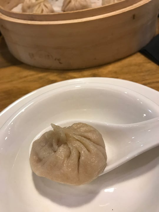 One of the xiao long bao, Shanghai-style soup dumplings, sits in a  spoon, ready to eat. Momo Mee restaurant, 110 E. Greenfield Ave., makes the broth and dough for the dumplings from scratch.