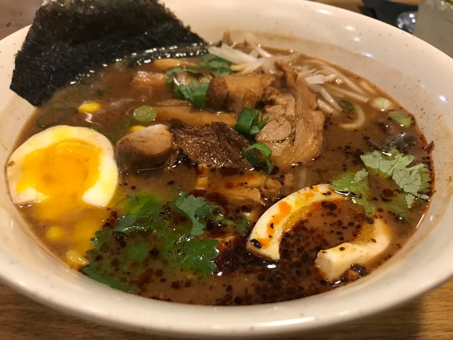 A splash of chile oil heats up the miso ramen, one of several kinds served at Momo Mee, 110 E. Greenfield Ave. The ramen noodles and broth are made at the restaurant, owned by chef Tony Ho.
