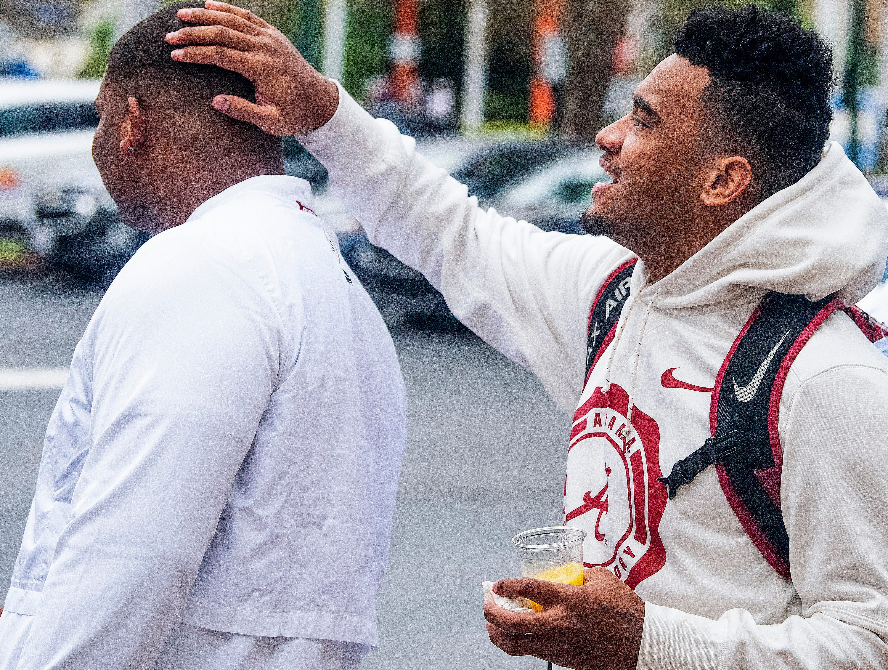 Alabama quarterback Tua Tagovailoa rubs the head of defensive lineman Quinnen Williams as they leave an Orange Bowl press conference in Fort Lauderdale, Fla., on Wednesday morning December 26, 2018.