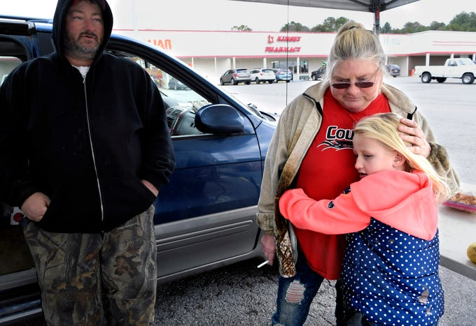 Rhonda Kisselburg, 51, comforts her granddaughter, Makayla, 7, who was not feeling well. Kisselburg's husband, Kent Kisselburg, 47, sells fruits and vegetables at a his stand in Ducktown on Dec. 4, 2018.