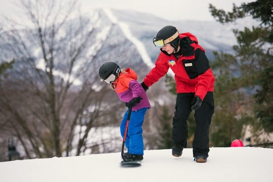 An instructor keeps it fun while teaching a younger to learn how to ski at Vermont's Smugglers Notch, known for its children's lesson programs.