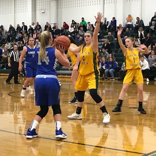 Holy Angels guard Caroline Staff (14) lines up a shot as Pascack Valley guard Brianna Smith (4) defends in the Joe Poli Holiday girls basketball tournament at Pascack Valley on Dec. 26, 2018. The home team won, 47-43.