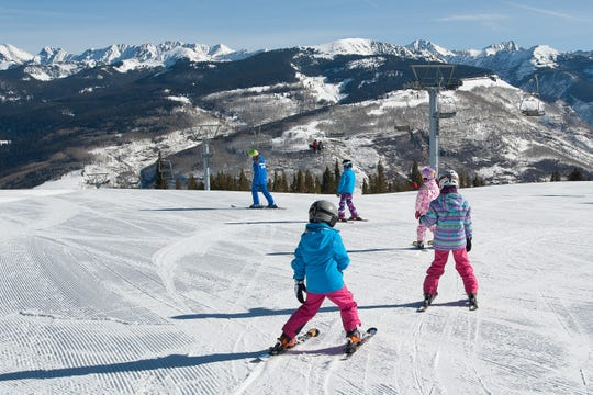 During a lesson at Vail Resorts (Colorado), an instructor leads a group of beginner students down a green trail that has a flatter pitch for easy turning surrounded by beautiful views.