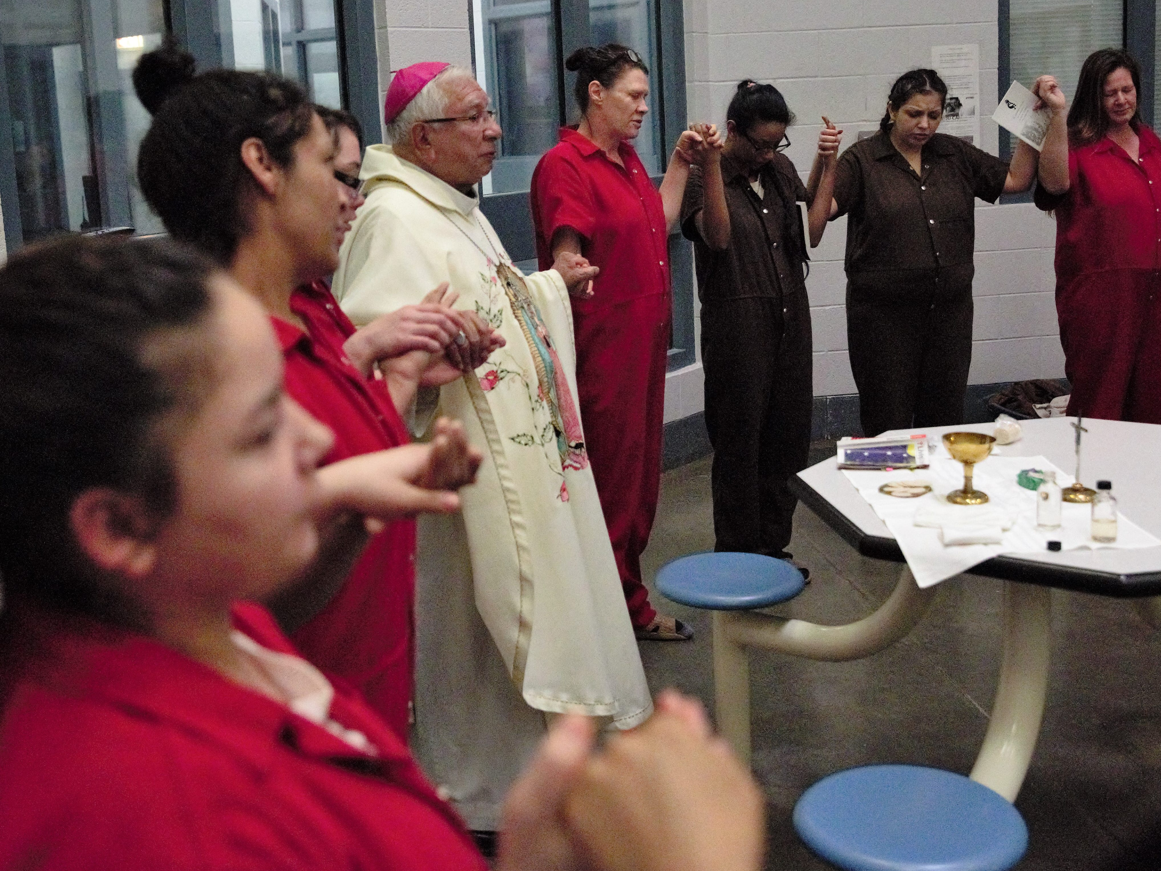 Inmates in the Doña Ana County Detention Center and Bishop Emeritus Ricardo Ramírez, center, hold hands to close out a Christmas Day church service inside the facility on Tuesday, Dec. 25, 2018.