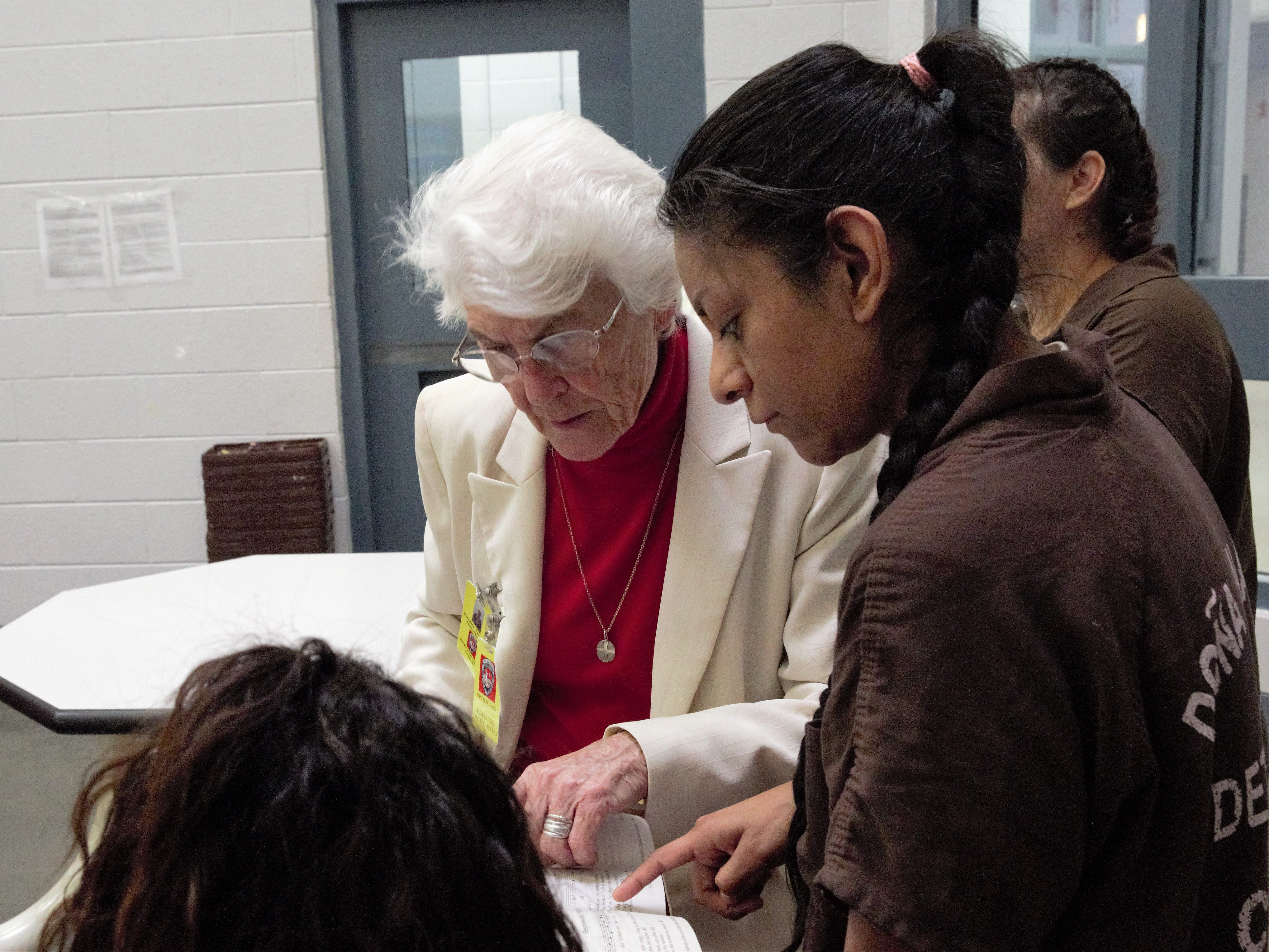 Sister Marie-Paule Willem, left, helps an inmate find her place in a prayer and song book on Tuesday, Dec. 25, 2018 in the Doña Ana County Detention Center in Las Cruces.