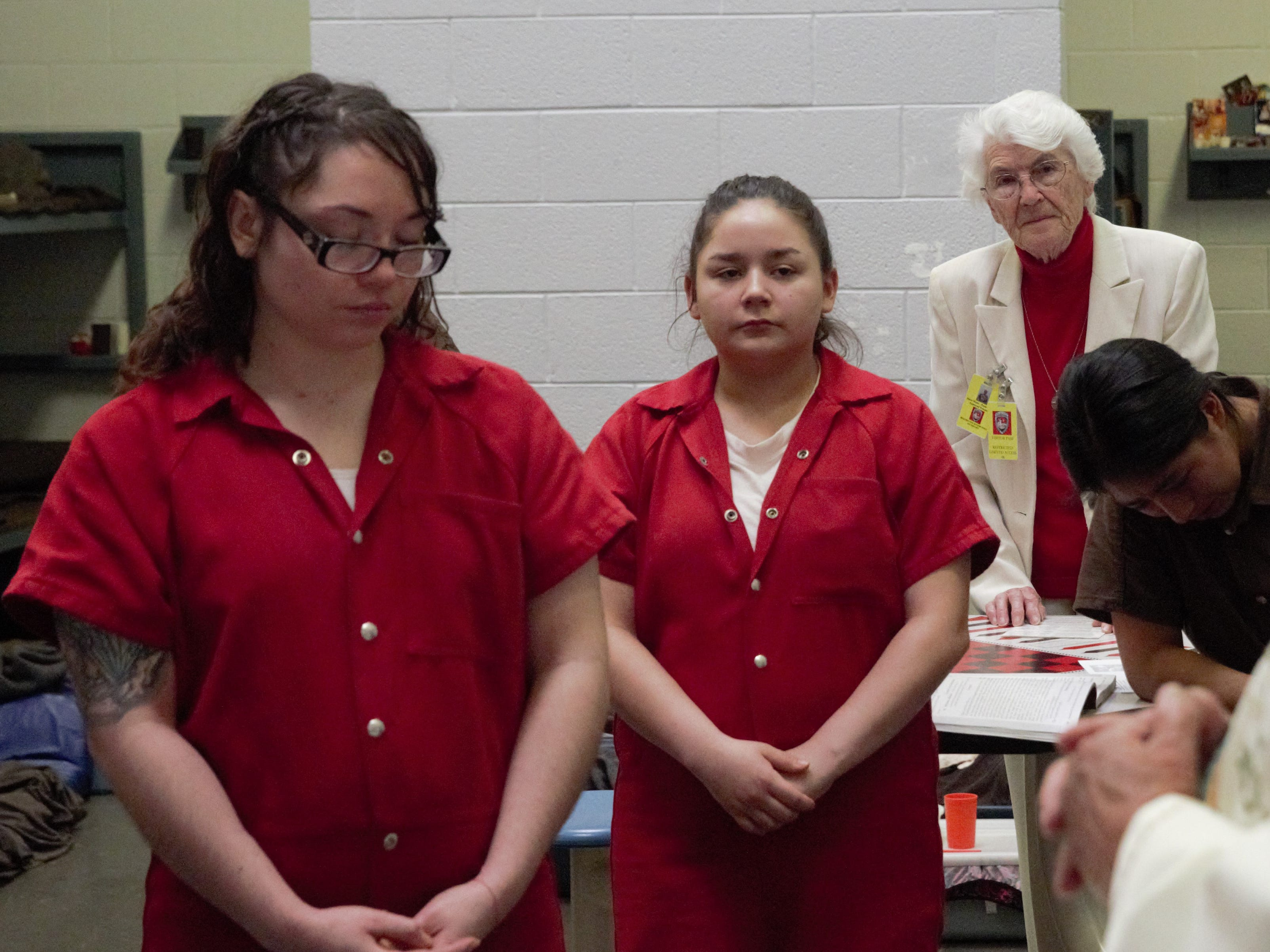 Sister Marie-Paule Willem, back, helps conduct a Catholic Mass for women inside a unit of the Doña Ana County Detention Center on Tuesday, Dec. 25, 2018.