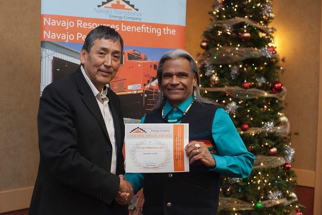 Navajo Transitional Energy Company governmental and external affairs director Steve Grey, left, recognizes Navajo Ministries President Raymond Dunton as a recipient for the NTEC Community Benefit Fund during a luncheon on Dec. 14 in Farmington.