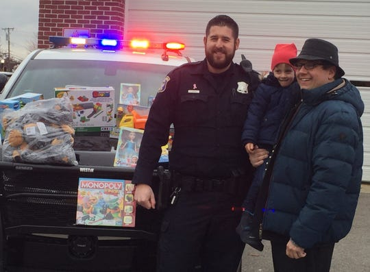 Gustav Neubacher, 4, and his father, Tobias, pose for photos with Plymouth Officer Josh Carroll before Carroll and Officer Mark Farhat set off on a Christmas Eve gift-distribution assignment. The Neubachers were visiting Plymouth from Salzburg, Austria.