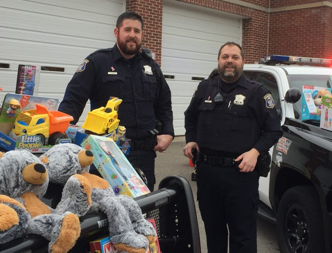 Officers Josh Carroll, left, and Mark Farhat arranged a display of Christmas gifts on the hoods of their patrol vehicles Monday before heading out to hand the toys out to unsuspecting motorists and their children.