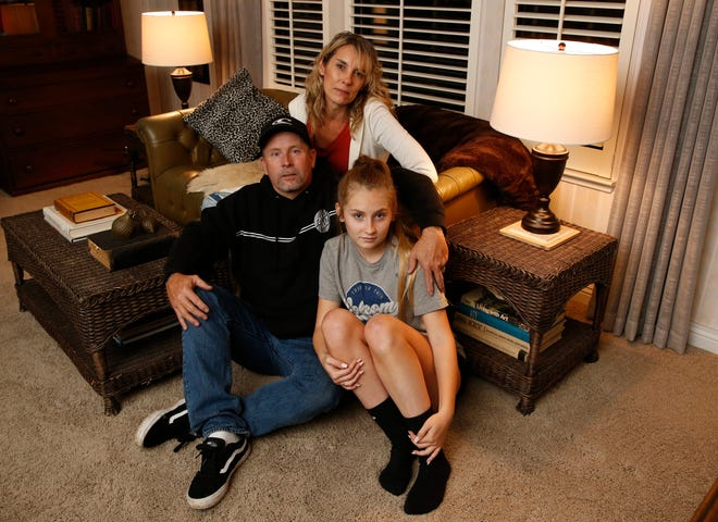 Jason James Burnett, accompanied by his daughter Faith and wife, Heather, poses at his mother-in-law's home in Chico on Nov. 26, 2018.