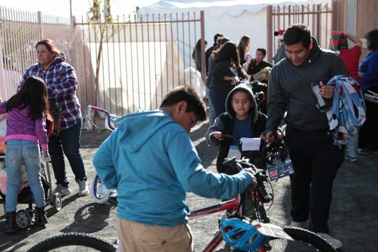 Children receive toys and bikes on Christmas at the Galilee Center in Mecca, Calif., Tuesday, December 25, 2018.