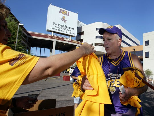 """LSU fan Jackson Sleet, of Los Angeles, purchases a T-shirt reading """"Two Teams One Goal"""" prior to entering Sun Devil Stadium before a game between the Sun Devil and Tigers on Sept. 10, 2005.)"""