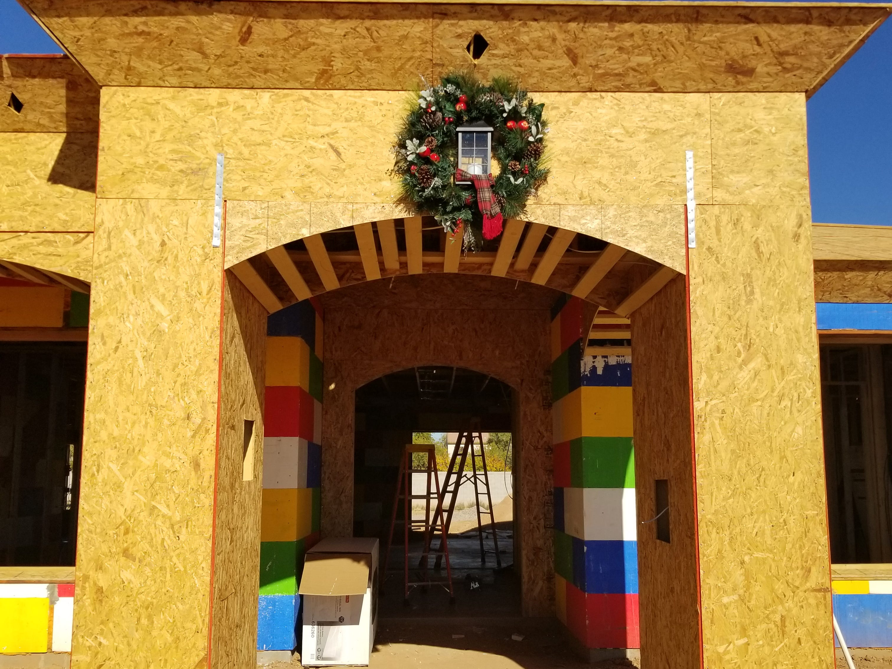 The home is partially framed out over insulating concrete forms, hollow foam blocks that can be stacked, reinforced with rebar and filled with concrete to form walls. A statuesque arched entrance sports a festive holiday wreath.